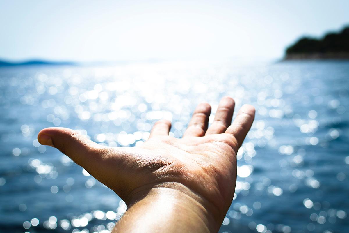 Hand Reaching Over Ocean